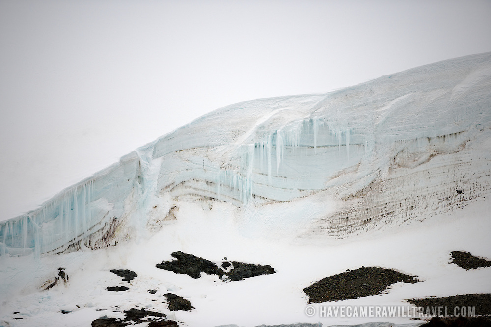 """Part of a snow-covered cliff that rises up next to the Lemaire Channel on the Antarctic Peninsula's western side. The Lemaire Channel is sometimes referred to as """"Kodak Gap"""" in a nod to its famously scenic views."""