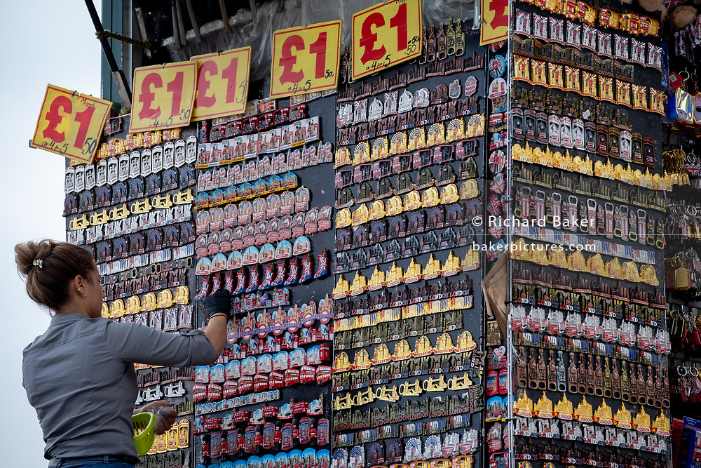 A street retailer adds to the display of £1 tourist trinket souvenirs at a kiosk at the end of Westminster Bridge during the Coronavirus pandemic when the tourism industry has hit hard the UK economy and associated jobs, on 16th September 2020, in London, England.