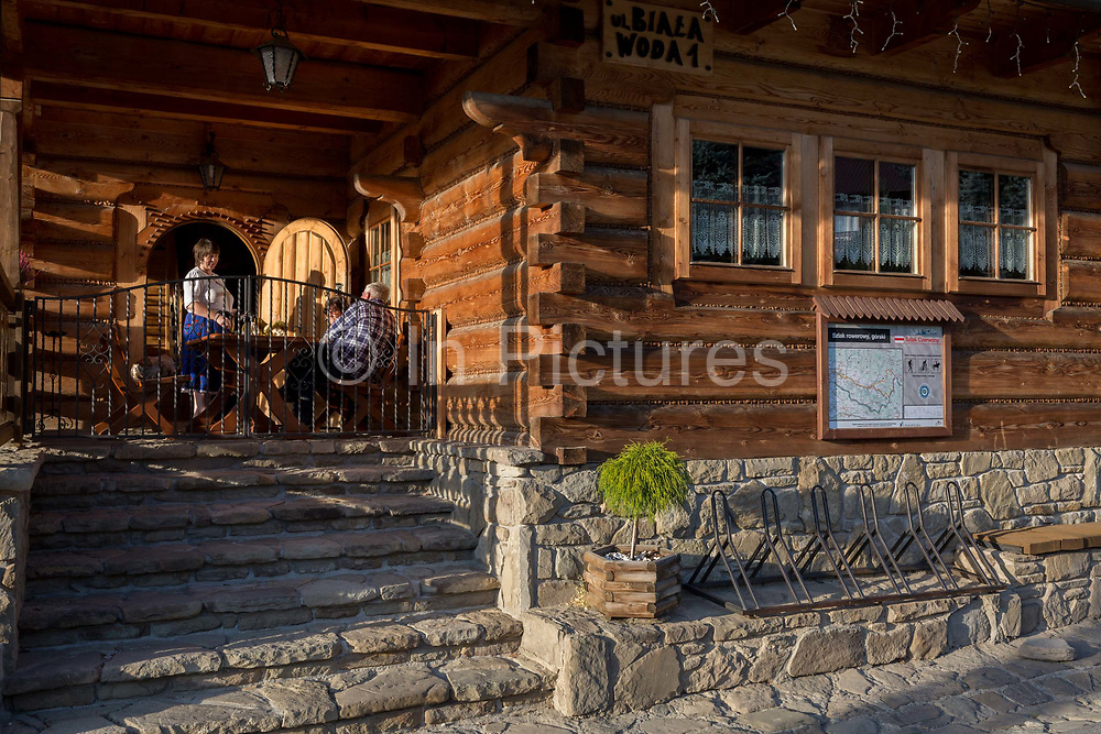 Customers enjoy late-afternoon sunshine outside the Bocowka restaurant, a traditional mountain log cabin in southern Poland, on 21st September 2019, in Jaworki, near Szczawnica, Malopolska, Poland.