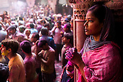 A woman prays quietly as Hindu's celebrate Holi in the Banke Bihari Temple in Vrindavan, in the Mathura district of Uttar Pradesh, India ,1st March 2010. <br />