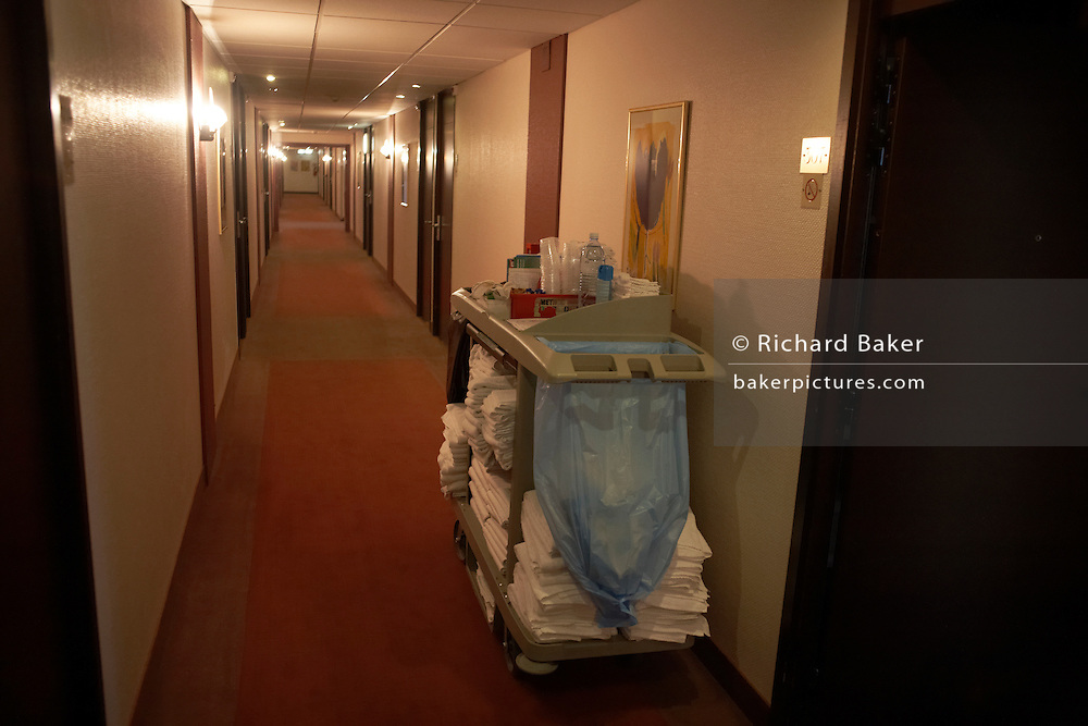 A chamber maid's trolley with cleaning supplies and equipment stands idle in the corridor of a Paris hotel.