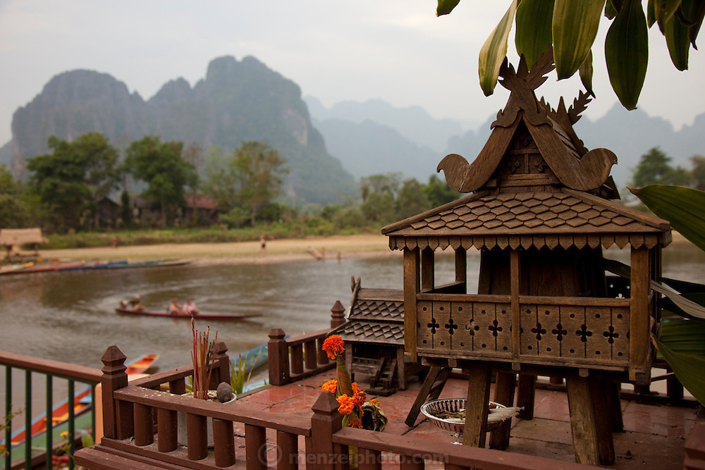 Vang Vieng, Laos. Nam Song River with karst formation mountains. A spriit house in the foreground is for offerings and incense.