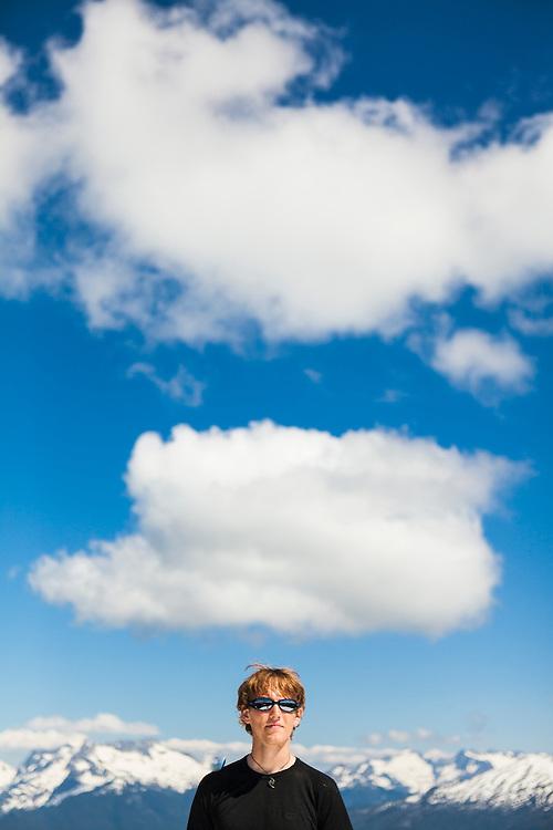 Ian Derrington stands under white fluffy clouds on the summit of Damnation Peak, North Cascades National Park, Washington.