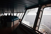 Crew members on the bridge pilot a large cruise ship in the waters of Finnmark region, northern Norway