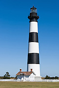 """The current Bodie Island Lighthouse (originally Body's Island, after the family name of the land seller) is the third that has stood in this vicinity of Bodie Island on the Outer Banks in North Carolina and was built in 1872. It stands 156 feet tall and is located on the Roanoke Sound side of the first island that is part of the Cape Hatteras National Seashore. The lighthouse is just south of Nag's Head. Its first order Fresnel lens focuses its 1000-watt bulb to be visible up to 19 miles. The US Coast Guard owns the tower, and the National Park Service owns the site. The lighthouse has white and black bands with a black lantern house. Cape Hatteras was once dubbed the """"Graveyard of the Atlantic"""" for its treacherous currents, shoals, and storms."""