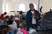 """A migrant looks at shoes that were donated to the temporary migrant shelter in Tultitlán, on August 3rd, 2012.  Tultitlán local authorithies ordered to dismantle the temporary shelter that was placed under a bridge in Tultitlán after shelter  """"San Juan Diego Cuauhtlatoatzin"""" in Lecheria, was closed on July 9th, 2012. (Photo: Prometeo Lucero)"""