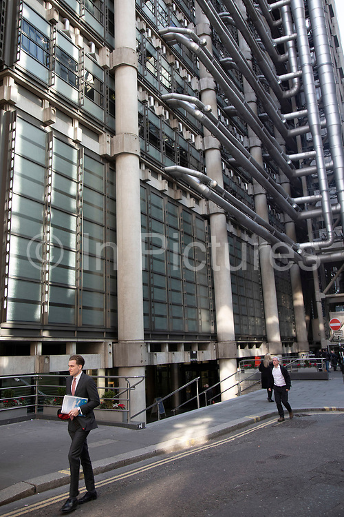 City workers pass underneath the Lloys Building in the City of London, United Kingdom. The Lloyds building also sometimes known as the Inside-Out Building is the home of the insurance institution Lloyds of London, and is located at 1, Lime Street. It was designed by architect Richard Rogers and built between 1978 and 1986. The building was innovative in having its services such as staircases, lifts, electrical power conduits and water pipes on the outside, leaving an uncluttered space inside.