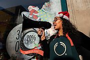 A lady wearing a Christmas hat promotes Black Friday savings outside Bodyshop on Londons Oxford Street on the 29th November 2019 in central London in the United Kingdom.