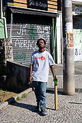 Young black Brazilian man standing in the street drinking a beer and smoking a cigarette, posing for a portrait looking at camera, Vila Madalena, Sao Paulo, Brazil.