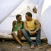 "Daphene Louis, an accountant and her boyfriend Steve Babtiste  who works in  customer care at Digicel at the  Catrine -Flon Camp, Puit-Blain St, Delmar 75, Port Au Prince. ""It was twenty-four hours after the quake before I saw my boyfriend. There were no communication networks and I had no way of knowing if he was dead or alive. When I saw him, I was so relieved I just jumped on him! Now we live in this camp under sheets held up with timber. It is very hard to get shelter from the sun,and when the rains come  there will be  no protection at all.  We need proper tents but even one month on we have been unable to get help. We have no privacy here, it's always noisy. We don't even have chance for a cuddle. It would be great to get a proper mattress, but we don't even have rice so that's not high up in our priorities."""
