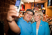 24 AUGUST 2010 -- TUCSON, AZ: A supporter of Gov Jan Brewer takes their photo with his cell phone camera in Tucson Tuesday. Gov Brewer made an appearance at Mr. An's Teppan Steak & Sushi in Tucson Tuesday night just as early returns in Arizona's primary elections were starting to come in. Brewer's victory has been credited to her signing SB 1070 and taking a tough stand on illegal immigration and against the Obama administration.   PHOTO BY JACK KURTZ
