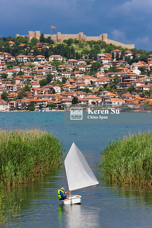 Sail boat and Tsar Samuil's Fortress with Ohrid cityscape on the shores of Lake Ohrid, Republic of Macedonia