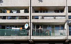 Leith, Edinburgh, Scotland, UK. 7 April 2020. In the third week of the nationwide coronavirus lockdown life in Leith continues although the streets are mostly deserted and shops closed. Pictured; Elderly man on balcony in his flat in Cables Wynd House apartment block.