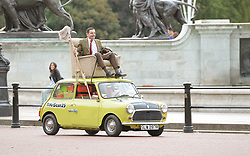 Mr Bean, played by Rowan Atkinson, celebrates the character's 25th anniversary on The Mall in front of Buckingham Palace, London, on his trademark Mini.