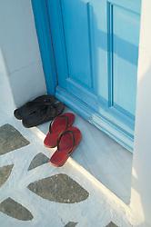 two sets of flip flops by a door in Greece