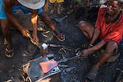 Making metal tools in Antandroy village. Houses are made from the Endemic Didiereacaea plants. Southern MADAGASCAR
