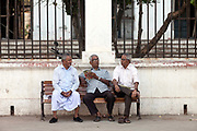Three old men sit and talk on a bench on the Promenade at Pondicherry, India. Pondicherry now Puducherry is a Union Territory of India and was a French territory until 1954 legally on 16 August 1962. The French Quarter of the town retains a strong French influence in terms of architecture and culture.