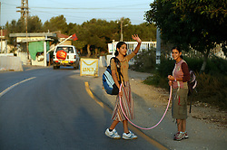 Two teenage girls approach the checkpoint outside the Nezer Hazani settlement, Gaza, Palestinian Territories, Nov. 6, 2004. Israel's parliament recently supported compensation payments for Jewish settlers leaving the Gaza Strip, in a vital vote for Prime Minister Ariel Sharon's plan to evacuate the occupied territory.