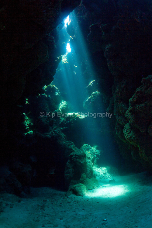 Rays of light shine down through a cave opening underwater at the Swan Islands, a tropical group of islands located 90 miles off the coast of Honduras.