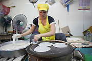 """Sept. 23, 2009 -- BANGKOK, THAILAND: A woman makes """"roti canai,"""" a type of Malaysian flat bread, in the Khlong Toey Market in Bangkok, Thailand. Khlong Toey Market is the largest market in Bangkok. Vendors sell everything from meat and fish to fruit and vegetables. They also sell clothes and dry goods in the market. Many working class Thais shop for food everyday because they don't have refrigerators and can't store food at home.   Photo by Jack Kurtz"""