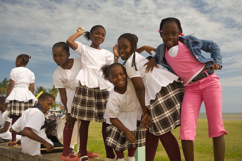 Girls in school uniforms on wall, Garifuna Settlement Day, annual festival held in late November, Dangriga, Stann Creek District, Belize, Central America