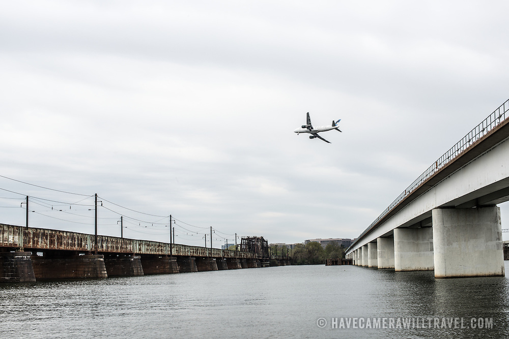 Two of the five bridges that make up what is commonly known as the 14th Street Bridge spanning the Potomac and connecting Washington DC with Virginia. at right is the Charles R. Fenwick Bridge which carries Washington Metro commuter trains. At left is the Long Bridge, which carries rail traffic. At center is a plane coming in to land at Reagan National Airport in Alexandria, VA.