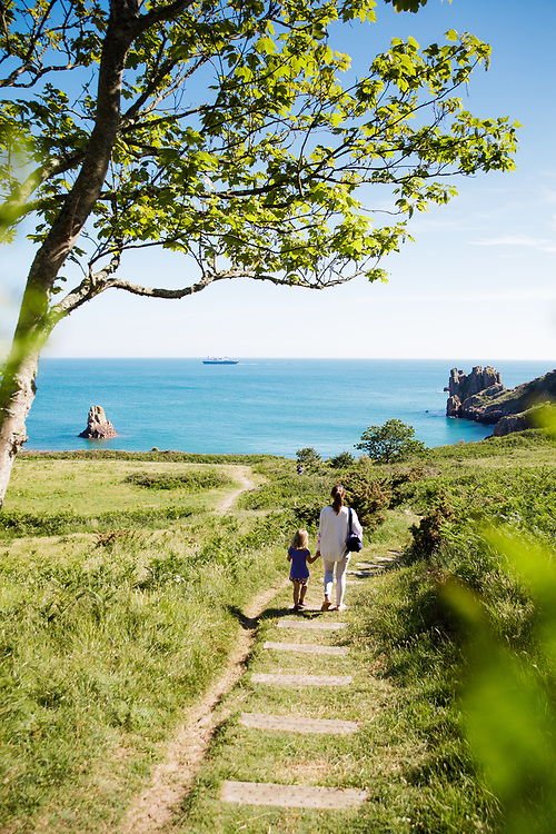 View through the trees of a Mum and child walking down the path to the  hidden paradise beach Beauport, with its calm blue sea great for paddle boarding and kayaking.
