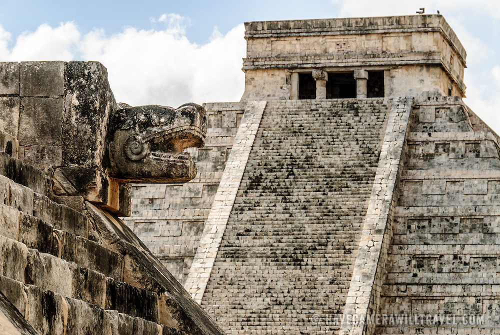In the background at right are the steps and top of the Temple of Kukulkan (El Castillo) and at left in the foreground are the carved jaguar heads of the Venus Platform at Chichen Itza Archeological Zone, ruins of a major Maya civilization city in the heart of Mexico's Yucatan Peninsula.