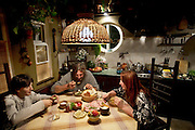 Art restorer  Vyacheslav ?Slava? Grankovskiy (center)  enjoys supper with his family in their house, near on Lake Ladoga, in Shlisselburg, near St. Petersburg, Russia. (From the book What I Eat: Around the World in 80 Diets.)  The caloric value of his day's worth of food in the month of October was 3900 kcals. He is 53; 6a feet two inches and 184 pounds. The son of a Soviet-era collective farm leader, he was raised near the Black Sea and originally worked as an artist and engineer. Over the years, he's learned a few dozen crafts, which eventually enabled him to restore a vast number of objects, build his own house, and be his own boss. His travel adventures have included crossing the Karakum Desert in Turkmenistan, where he spent time with a blind hermit and dined with a Mongol woman who hunted bears and treated him to groundhog soup. His favorite drink: Cognac. Does he ever drink soda? ?No, I use cola in restoration to remove rust, not to drink,? he says.