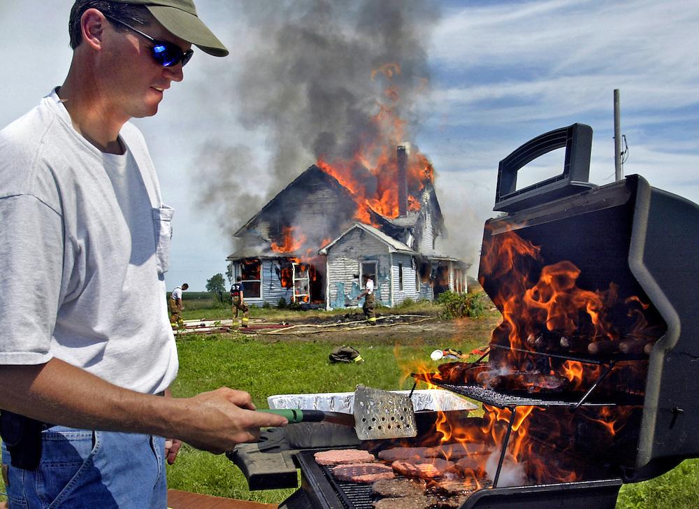Danville Firefighter Frain (cq) Wagner grills lunch as fellow firefighters burn a house for training Saturday, June 12, 2004, outside Danville, Iowa. Scott Morgan   The Hawk Eye