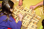 four Children aged 6 - 8, building with Kapla wooden construction blocks, the KAPLA plank, only one size, is best adapted for building without gluing or fixing.