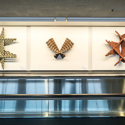 Art pieces by Barbara Homes mounted on a wall above a moving walkway in Terminal 3 of San Francisco's International Airport. The items are part of an exhibit titled the Art of Recology: The Artist in Residence Program 1990-2013 that makes use of reclaimed and recycled materials.