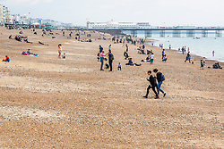 © Licensed to London News Pictures. 25/05/2019. Brighton, UK.  Members of the public take advantage of the occasional rays of sunshine by spending time on the beach on the May Bank holiday Saturday. Photo credit: Hugo Michiels/LNP