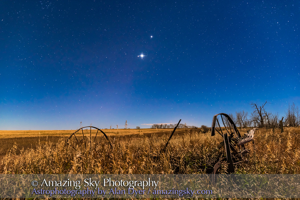 The planet trio of Venus (brightest), Jupiter (above Venus) and Mars (dim and red to the left of Venus), all in Leo in the morning sky on November 1, 2015, with the waning gibbous Moon illuminating the landscape and sky. Even in the moonlight, the Zodiacal Light seems to be faintly visible along the ecliptic defined by the line of planets. <br /> <br /> This is a stack of 6 x 30-second exposures at f/5.6 and ISO 2500 for more depth of the field for the ground, plus a 13-second exposure at f/2.5 and ISO 800 to minimize star trailing. The ground exposures were mean combined in a stack to smooth noise. Diffraction spikes added with Astronomy Tools Actions for Photoshop.