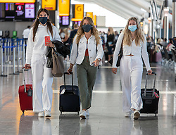 © Licensed to London News Pictures. 24/07/2020. London, UK. Three young travellers wear masks in Terminal 5 at London Heathrow on their way to Nice for a two week holiday as face masks become compulsory today in airports, shops, takeaway cafes and supermarkets and enforced by the Police, with anyone who fails to wear one liable to a £100 fine. Photo credit: Alex Lentati/LNP