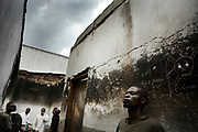 As the majority of sex offenders are armed men - both rebels and soldiers - out of more than 14,000 rape cases a year, only a very handful of suspects are put in prison in Goma, which holds 700 prisoners with various criminal charges. Omari Konglo, 27, right, and other accused rapists from the Congolese Army (FARDC) stand by the charred wall inside Goma's Central Prison in March 2009 where it was burnt from the riot the year before. The prison did not have the exact number of those who were charged with sexual violence. Some men were imprisoned simply because they were arrested by the Police of Women and Children, others were attending their court appearance for audiences, and others were sentenced for several years.