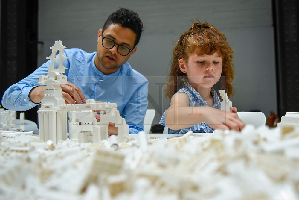 """© Licensed to London News Pictures. 26/07/2019. LONDON, UK. Daisy Lenkiewicz, aged 6, and her father Simon work with Lego at the preview of """"The cubic structural evolution project"""", 2004, by Olafur Eliasson at Tate Modern.  Exhibited for the first time in the UK, the artwork comprises one tonne of white Lego bricks inspiring visitors to create their own architectural vision for a future city and is on display until 18 August 2019.  The work coincides with the artist's new retrospective exhibition """"In real life"""" at Tate Modern on display to 5 January 2020.  Photo credit: Stephen Chung/LNP"""