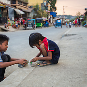 CAPTION: In Marikina City, everywhere is a potential playground for children. The local government has started to improve the drains under these boys' feet in order to reduce the impact of flooding. However, Hilda feels that its measures to prevent flooding in their community could be implemented far faster. LOCATION: Ampalaya Street, Barangay Tumana, Marikina City, Philippines. INDIVIDUAL(S) PHOTOGRAPHED: Unknown.