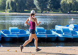 Licensed to London News Pictures. 16/09/2021. London, UK. A runner enjoys the late summer sun in Hyde Park, London as weather forcasters predict a warmer few days ahead with highs of 24c for London and the South East. Photo credit: Alex Lentati/LNP