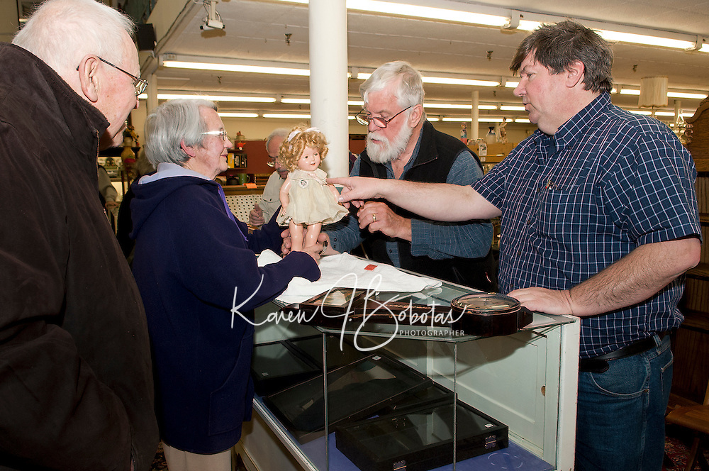Vick and Irene Fournier present a 1930's Shirley Temple doll to Doug McGowan and Bruce Baier during Laconia Historical Society's Appraisal Night at the Laconia Antique Center Tuesday evening.  (Karen Bobotas/for the Laconia Daily Sun)