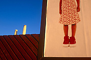 The legs of a young girl appear on an ad billboard, echoing two of the chimneys of Battersea Power Station. It is early morning in this part of south London that is soon to be redeveloped to accommodate the New US Embassy at Nine Elms. But here we see the kids' fashion advertisement juxtaposed with the post-industrial structure that has been a famous London landmark since the 1930s. Battersea was once a coal-fired power station providing the well known, four chimney layout. The station was decommissioned from generating electricity in 1983 but used in The Beatles' 1965 movie Help! and on the cover of Pink Floyd's 1977 album Animals.