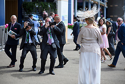 © Licensed to London News Pictures. 21/06/2018. London, UK. Photographers photograph a woman in an elaborate hat at Ladies Day at Royal Ascot at Ascot racecourse in Berkshire, on June 21, 2018. The 5 day showcase event, which is one of the highlights of the racing calendar, has been held at the famous Berkshire course since 1711 and tradition is a hallmark of the meeting. Top hats and tails remain compulsory in parts of the course. Photo credit: Ben Cawthra/LNP