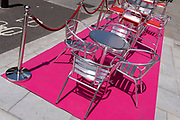 A pink carpet with silver street tables and seating stretches uphill in Aldwych, on 23rd June 2021, in Westminster, London, England.