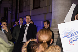 London, UK. 12th February, 2019. Guests wait outside the Gadson Club in Pall Mall where Justice Secretary David Gauke was due to host a reception whilst members and supporters of grassroots trade union United Voices of the World protest outside against his refusal to negotiate with the trade union over their demands for the London Living Wage, annual leave and sick pay for outsourced cleaners, security guards and receptionists working at the Ministry of Justice, all of whom have been on strike for varying periods recently. The Gadson Club is the official alumni club for the Oxford University Conservative Association.