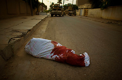 The wrapped body of a man shot in the head and dumped on a side street in Adhamiya is discovered by a passing American patrol on Thursday April 27, 2007.
