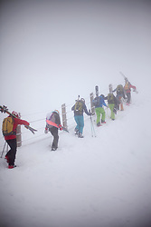 Group if skiers carrying ski gear on mountain slope