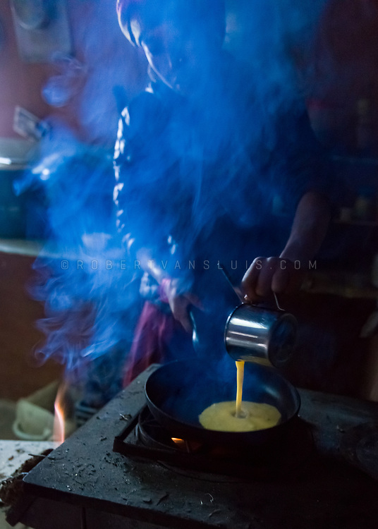 A woman cooking an omelette in a trekkers lodge in the Nepal Himalaya. Photo © robertvansluis.com