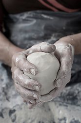 Close-up of female potter's hand holding clay, Bavaria, Germany