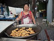 23 JUNE 2015 - BANGKOK, THAILAND: A vendor making Chinese doughnuts, called Pa Thong Ko, in the market in the Wong Wian Yai train station in the Thonburi section of Bangkok.    PHOTO BY JACK KURTZ