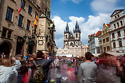 Mostly visitors are watching a street perfomer blowing bubbles in-front of the Old Town hall at Old Town Square in Prague.
